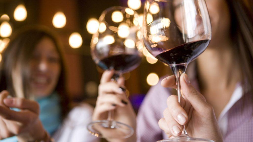 women swirling red wine in glasses