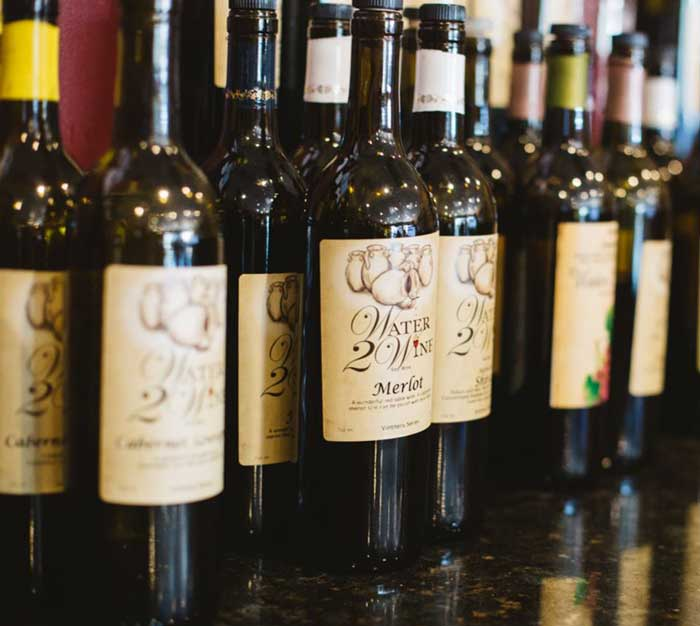 wine bottles on bar at water 2 wine Austin winery with labels and small batch wines