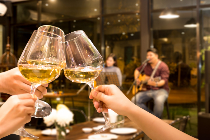 three glasses of white wine in focus with guitar and singers blurred in background at winery