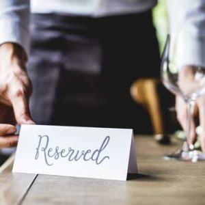 man standing with reserved sign at table at winery