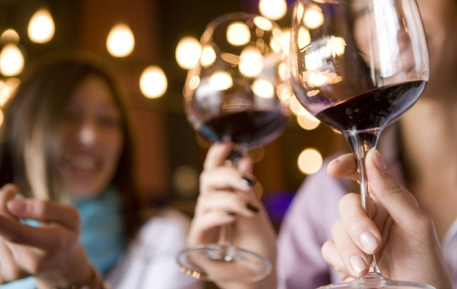 swirling wine in glasses at private party rental at winery
