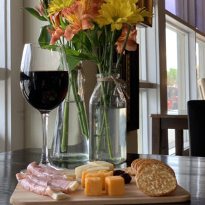 cheese tray with crackers and red wine