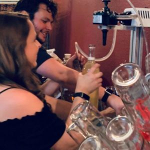 couple bottling wine at small winery